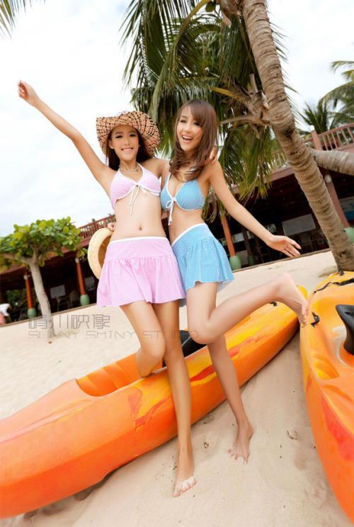 沙滩上两个可爱的双胞胎美女姐妹花